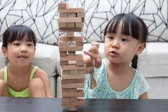 Asian Chinese little sisters playing wooden stacks. At home stock photo