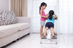 Asian Chinese little sisters playing workout machine in the living room. At home stock photos