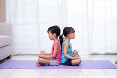 Asian Chinese little sisters practicing yoga pose on a mat. In the living room at home stock photography