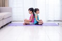 Asian Chinese little sisters practicing yoga pose on a mat. In the living room at home royalty free stock photos