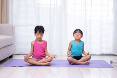 Asian Chinese little sisters practicing yoga pose on a mat. In the living room at home stock photos