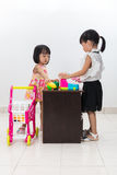 Asian Chinese little sisters pretending customer and cashier wit Royalty Free Stock Photos