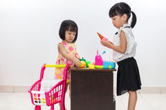 Asian Chinese little sisters pretending customer and cashier wit. Asian Chinese little sisters pretending as customer and cashier with trolley toys in isolated Royalty Free Stock Images