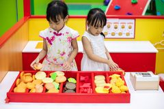 Asian Chinese little sisters role-playing at burger store. At indoor playground stock photo