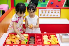 Asian Chinese little sisters role-playing at burger store. At indoor playground royalty free stock photography