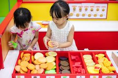 Asian Chinese little sisters role-playing at burger store. At indoor playground stock photos