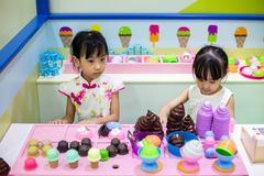 Asian Chinese little sisters role-playing at ice cream store. At indoor playground royalty free stock photos