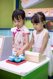 Asian Chinese little sisters role-playing at sushi store. At indoor playground royalty free stock photos