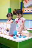 Asian Chinese little sisters role-playing at sushi store. At indoor playground royalty free stock photo