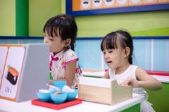 Asian Chinese little sisters role-playing at sushi store. At indoor playground stock images