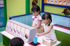 Asian Chinese little sisters role-playing at sushi store. At indoor playground royalty free stock image