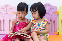 Asian Chinese little sisters sitting on the floor reading Royalty Free Stock Photo