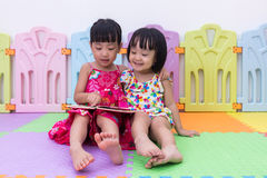 Asian Chinese little sisters sitting on the floor reading. At home royalty free stock photography