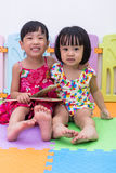 Asian Chinese little sisters sitting on the floor reading Royalty Free Stock Image