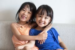 Asian Chinese little sisters sitting on the sofa. In the living room at home Royalty Free Stock Images