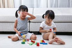 Asian Chinese little sisters struggle for blocks. On the floor in the living room at home stock photo