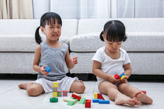 Asian Chinese little sisters struggle for blocks. On the floor in the living room at home stock photography