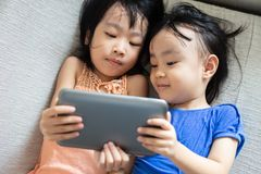 Asian Chinese little sisters using tablet lying on the sofa. In the living room Royalty Free Stock Photo