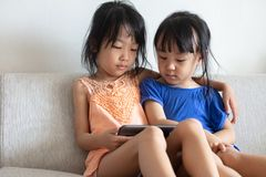 Asian Chinese little sisters using tablet on the sofa. In the living room royalty free stock photos