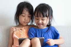 Asian Chinese little sisters using tablet on the sofa. In the living room royalty free stock image