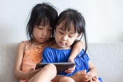 Asian Chinese little sisters using tablet on the sofa. In the living room royalty free stock images