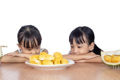 Asian Chinese little sisters waiting to eat durian fruit. In isolated white background stock photos