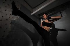 Asian chinese mafia girl performing a kick royalty free stock image