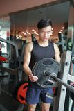 Asian chinese man in gym Increase the weight of the dumbbell. Man in gym try Increase the weight of the dumbbell Royalty Free Stock Photography