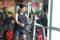 Asian chinese man in gym Increase the weight of the dumbbell. Man in gym try Increase the weight of the dumbbell Stock Image