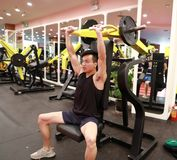 Asian chinese man in gym lifting weights. Man in gym try with dumbbells Stock Image