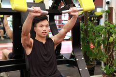 Asian chinese man in gym lifting weights. Man in gym try with dumbbells Royalty Free Stock Images