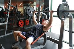 Asian chinese man in gym lifting weights. Man in gym try with dumbbells Stock Images