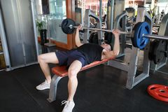 Asian chinese man in gym lifting weights. Man in gym try with dumbbells Stock Photo