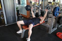 Asian chinese man in gym lifting weights. Man in gym try with dumbbells Royalty Free Stock Photo