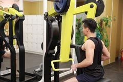 Asian chinese man in gym lifting weights. Man in gym try with dumbbells Royalty Free Stock Image