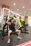 Asian chinese man in gym lifting weights. Man in gym try with dumbbells Stock Photography