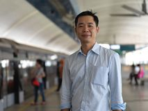 Asian chinese man smiling and waiting to go to work via train. Asian chinese man smiling and waiting for train transport Royalty Free Stock Images