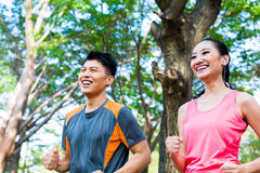 Asian Chinese man and woman jogging in city park Stock Photos