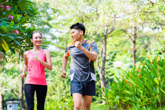 Asian Chinese man and woman jogging in city park. Asian Chinese men and women jogging in city park royalty free stock image