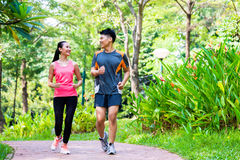 Asian Chinese man and woman jogging in city park. Asian Chinese men and women enjoy jogging in city park stock images