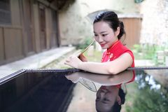 Asian Chinese chi-pao cheongsam woman with classical embroidered fan enjoy relaxed free time in ancient town inverted reflection. Asian Chinese model female royalty free stock photography