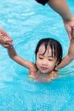 Asian Chinese Mom Teaching Little Girl Swimming At The Pool. Asian Chinese Mom Teaching Little Girl Swimming At The Outdoor Pool stock photography