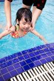 Asian Chinese Mom Teaching Little Girl Swimming At The Pool. Asian Chinese Mom Teaching Little Girl Swimming At The Outdoor Pool stock photo