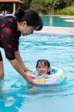 Asian Chinese Mom Teaching Little Girl Swimming At The Pool. Asian Chinese Mom Teaching Little Girl Swimming At The Outdoor Pool stock images