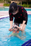 Asian Chinese Mom Teaching Little Girl Swimming At The Pool. Asian Chinese Mom Teaching Little Girl Swimming At The Outdoor Pool royalty free stock images