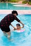 Asian Chinese Mom Teaching Little Girl Swimming At The Pool. Asian Chinese Mom Teaching Little Girl Swimming At The Outdoor Pool stock photos