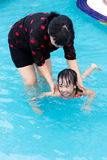 Asian Chinese Mom Teaching Little Girl Swimming At The Pool. Asian Chinese Mom Teaching Little Girl Swimming At The Outdoor Pool royalty free stock photography