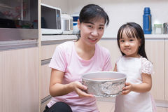 Asian Chinese mother and daughter baking cake together. At home in the kitchen Stock Image