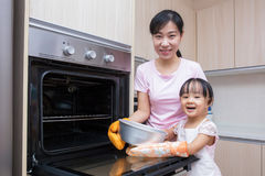 Asian Chinese mother and daughter baking cake together Royalty Free Stock Photos