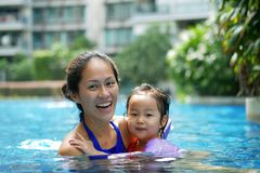 Asian Chinese Mother and Daughter bonding in the swimming pool smiling happy stock photo